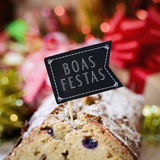 Text boas festas, happy holidays in portuguese. Closeup of a fruitcake topped with a flag-shaped signboard with the text boas festas, happy holidays written in Royalty Free Stock Photos