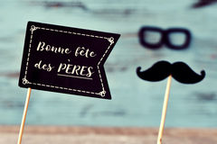 Text bonne fete des peres, happy fathers day in french. A black flag-shaped signboard with the text text bonne fete des peres, happy fathers day in french, and a stock image