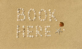Text BOOK HERE written in sand Royalty Free Stock Photos