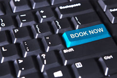 Text of book now on blue button. Close up of modern keyboard with text of book now on the blue button Royalty Free Stock Images