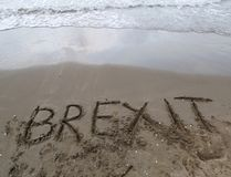 Text BREXIT on the sand of the sea waiting to be erased by the w. Big text BREXIT on the sand of the sea waiting to be erased by the water of the sea royalty free stock photo