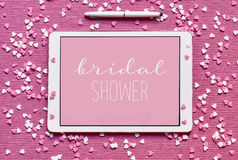 Text bridal shower in a tablet computer. High-angle shot of a tablet with the text bridal shower written in white in it against a pink background, placed on a Stock Photography