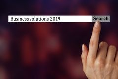 The text in the browser shows `Business solutions 2019`.A woman hand shows the terms you should investigate in 2019. stock photos