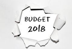 Text `Budget` with year 2018 into the torn paper. Hand written text and year in black color into the center side of torn paper sheet. This displays Budget 2018 Stock Photo