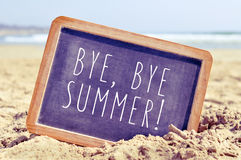Text bye, bye summer in a chalkboard on the beach Royalty Free Stock Image