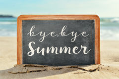 Text bye, bye summer in a chalkboard on the beach Royalty Free Stock Photos
