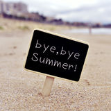 Text bye, bye summer in a signboard on the beach Royalty Free Stock Image