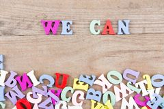 Text. `We can` of colored wooden letters on a wooden background Stock Image