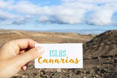 Text Canary Islands in signboard in dry landscape. Closeup of the hand of a caucasian man holding a signboard with the text Islas Canarias, Canary Islands royalty free stock images