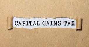 text CAPITAL GAINS TAX, on torn paper