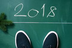 Text chalk 2018 and black sneakers from above on a green blackboard. Stock Photos