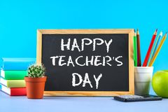 Text chalk on a chalkboard: Happy Teacher's Day. School supplies, office, books, apple. Text chalk on a chalkboard: Happy Teacher's Day. School supplies, office Stock Images