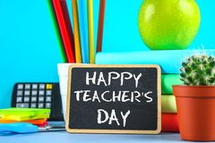 Text chalk on a chalkboard: Happy Teacher`s Day. School supplies, office, books, apple. Text chalk on a chalkboard: Happy Teacher`s Day. School supplies, office Royalty Free Stock Images