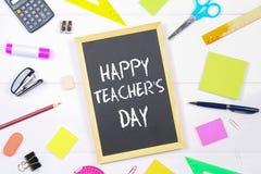 Text chalk on a chalkboard: Happy Teacher's Day. School supplies, office, books, apple. Text chalk on a chalkboard: Happy Teacher's Day. School supplies, office Stock Photo