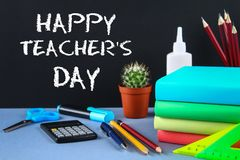 Text chalk on a chalkboard: Happy Teacher's Day. School supplies, office, books, apple. Text chalk on a chalkboard: Happy Teacher's Day. School supplies, office Royalty Free Stock Photo