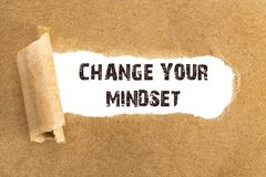 The text CHANGE YOUR MINDSET appearing behind torn brown paper.  royalty free stock images