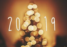 2019 text on christmas tree golden lights in festive room, blur. Bokeh of glowing decoration on tree branches. Happy New Year. Season`s greetings card. Merry royalty free stock photo