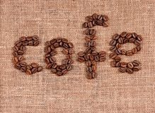 Text of coffee beans. On natural burlap texture Stock Photos