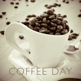 Text coffee day and cup full of roasted coffee beans Royalty Free Stock Photography