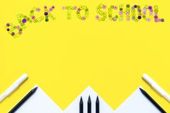 Text from the color buttons back to school on a yellow background with white paper, black pencils and white pens.  stock photo