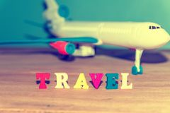 Text in colored letters - travel, on the background of a toy airplane, photo with summer tint.  royalty free stock images