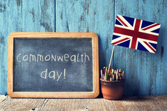 Text commonwealth day in a chalkboard. A wooden-framed chalkboard with the text commonwealth day written in it and the Union Flag in a pot of pencils, against a Royalty Free Stock Photo