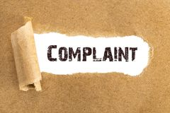 The text Complaint appearing behind torn brown paper.  royalty free stock image