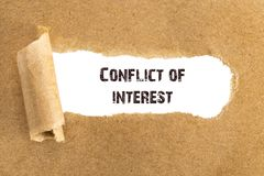 The text Conflict of interest appearing behind torn brown paper.  stock photo