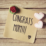 Text congrats mom in a note. Closeup of a piece of paper with the text congrats mom written in it, some heart-shaped marshmallows and a red rose on a rustic royalty free stock photo