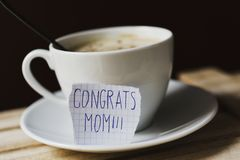 Text congrats mom in a piece of paper. Closeup of a piece of paper with the text congrats mom written in it, next to a white ceramic cup with cappuccino stock photo