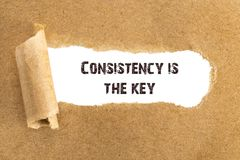 The text Consistency is the key appearing behind torn brown paper.  royalty free stock photos