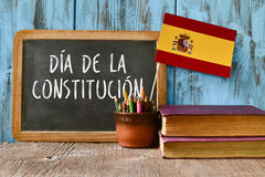 Text constitution day written in spanish. A chalkboard with the text dia de la constitucion, constitution day written in spanish, a pot with pencils, the flag of stock photo