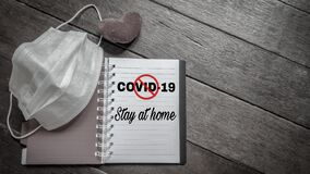 text covid-19 stay at home with stop sign written on notepad