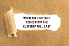The text When the customer comes first the customer will last ap. Pearing behind torn brown paper stock photography
