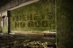 Text där är ingen gud på den smutsiga väggen i ett övergett förstört hus Royaltyfri Foto