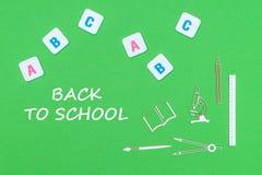 Text de volta à escola, de cima das fontes de escola de madeira dos minitures e das letras do ABC no fundo verde imagens de stock