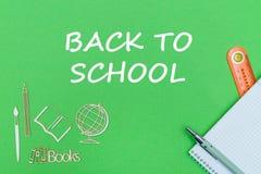 Text de volta à escola, miniaturas de madeira das fontes de escola, caderno no fundo verde fotos de stock