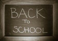 Text de volta ao conceito da escola escrito no quadro com quadro de madeira imagem de stock