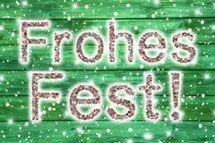 Text der frohen Weihnachten in der deutschen Sprache auf hölzernem grünem backgrou Stockfotografie