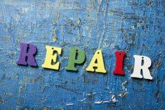 Text der REPARATUR auf buntem hölzernem ABC-Buchstaben am abstrakten Schmutzblauhintergrund Stockfotografie