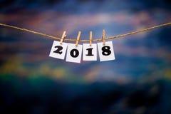 Text des guten Rutsch ins Neue Jahr 2018 auf Papieren mit Wäscheklammern auf dem Unschärfezusammenfassung blauen bokeh Hintergrun Stockbild