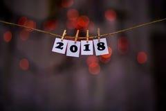 Text des guten Rutsch ins Neue Jahr 2018 auf Papieren mit Wäscheklammern mit Girlande bokeh auf Hintergrund Lizenzfreie Stockfotos