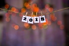 Text des guten Rutsch ins Neue Jahr 2018 auf Papieren mit Wäscheklammern mit Girlande bokeh auf Hintergrund Lizenzfreie Stockbilder