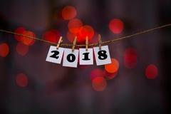 Text des guten Rutsch ins Neue Jahr 2018 auf Papieren mit Wäscheklammern mit Girlande bokeh auf Hintergrund Stockbild