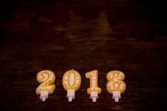 Text des guten Rutsch ins Neue Jahr 2018 von den Kerzen auf hölzernem Hintergrund Stockfotografie