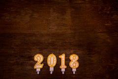 Text des guten Rutsch ins Neue Jahr 2018 von den Kerzen auf hölzernem Hintergrund Lizenzfreies Stockfoto