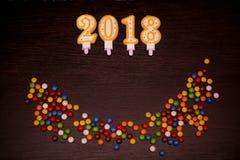 Text des guten Rutsch ins Neue Jahr 2018 von den Kerzen mit bunten Süßigkeiten auf hölzernem Hintergrund Lizenzfreie Stockfotografie