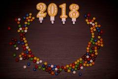 Text des guten Rutsch ins Neue Jahr 2018 von den Kerzen mit bunten Süßigkeiten auf hölzernem Hintergrund Stockbilder