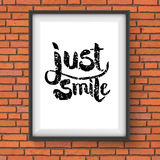 Text Design for Just Smile Concept on a Frame. Close up Black Text Design for Just Smile Concept on a Rectangular Frame Hanging on a Brick Wall Stock Image
