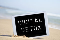 Text digital detox in a tablet computer, in the sand of a beach. A tablet computer with the text digital detox written in its screen, placed in the sand of a Stock Image